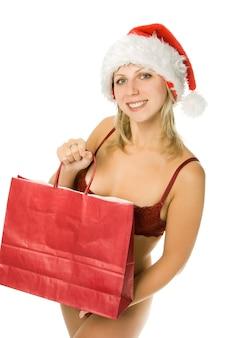 Sexy kerst meisje in ondergoed met cadeau in rode hoed geïsoleerd op witte achtergrond