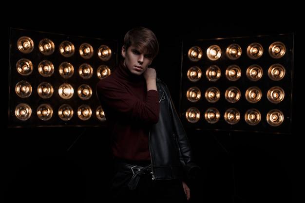 Sexy knappe jongeman met een modieus kapsel in een stijlvolle leren jas in rode golf en modieuze broek is in een donkere binnenshuis tegen een achtergrond van fel oranje schijnwerpers. aantrekkelijke kerel