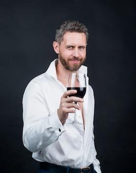 Sexy knappe man in wit overhemd houdt glas rode wijn vast, liefdesdatum.