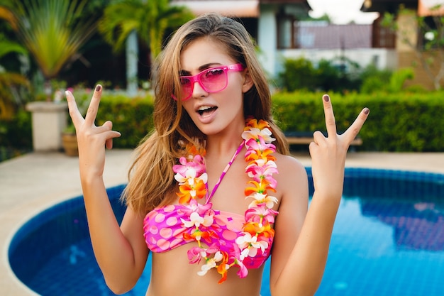 Sexy lachende vrouw op zomervakantie met plezier bij zwembad dragen van bikini en roze zonnebril, tropische bloemen op hawaï, kleurrijke zomer mode-stijl