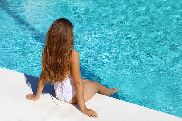 Sexy langharige jonge vrouw met witte zwembroek zitten ontspannen in het zwembad