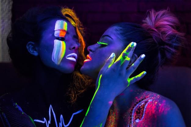 Sexy lesbische fashion modellen in uv neon licht met fluorescerende gloeiende body art make-up zoenen. rustig donker beeld. soft focus afbeelding.