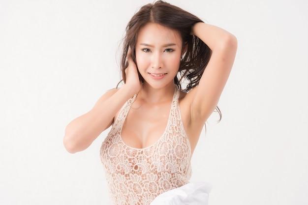 Sexy levensstijl portret van mooie verleidelijke jonge vrouw bruin langharige in witte kanten jurk staan op witte gordijnen curtain
