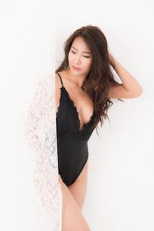 Sexy levensstijl portret van mooie verleidelijke jonge vrouw bruin langharige in zwarte sexy bodysuit staan op witte gordijnen curtain