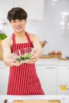 Sexy lgbt homo jonge aziatische man met rode schort houdt verse salade op handen na het koken in de keuken. nake lachende man kookt gezond voedsel voor zijn partner. mooie homoseksuele familie van hetzelfde geslacht in het weekend.