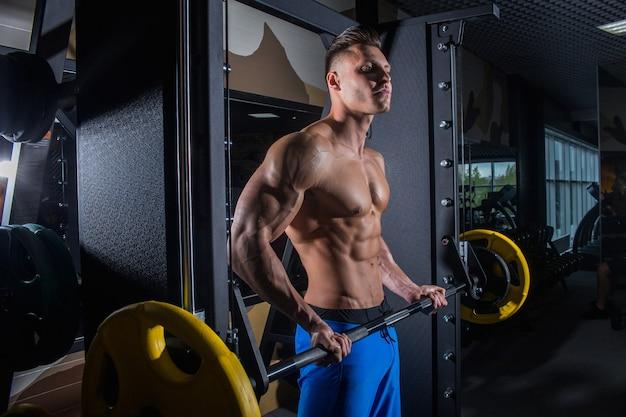 Sexy man in de sportschool met halters. sportieve man met grote spieren en brede rug traint in de sportschool