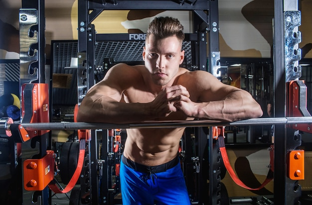 Sexy man in de sportschool met halters. sportieve man met grote spieren en een brede rug traint in de sportschool