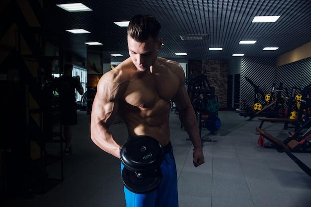 Sexy man in de sportschool met halters. sportieve man met grote spieren
