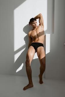 Sexy man in zwart slipje met een opgepompt lichaam bij het raam