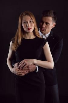 Sexy man knuffelt een charmante roodharige vrouw van achteren