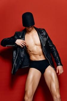 Sexy man met een opgepompte torso in een leren jas en korte broek