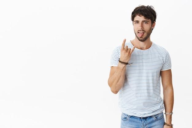 Sexy mannelijke mannelijke muzikant in gestreept t-shirt met blauwe ogen en borstelharen met rock-n-roll-gebaar dat zijn tong uitsteekt en koel en chill handelt, zelfvoldaan terwijl hij omringd is met fans