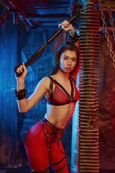 Sexy meesteres in rode bdsm lingerie houdt lederen zweep, verlaten fabrieksinterieur. jong meisje in erotisch ondergoed, sexfetisj, seksuele fantasie