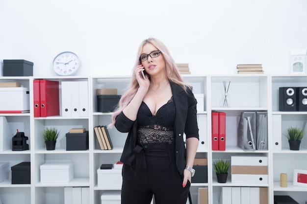 Sexy meisje beantwoordt oproepen en werkt op kantoor