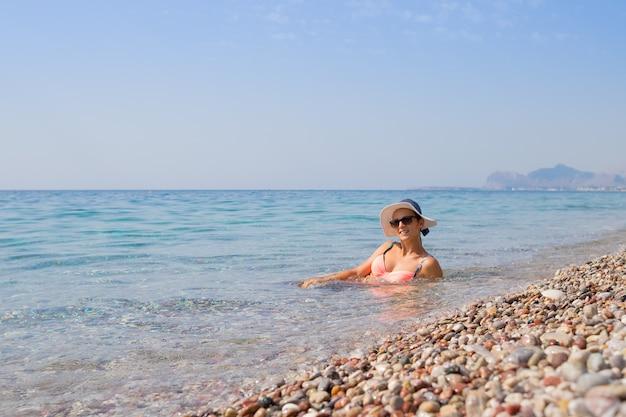 Sexy meisje dat bikini en hoed draagt en van water geniet bij kiezelsteenstrand