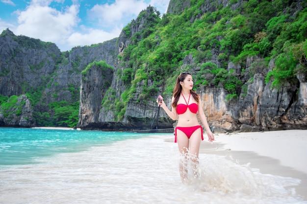 Sexy meisje dat een rode bikini draagt bij het strand.