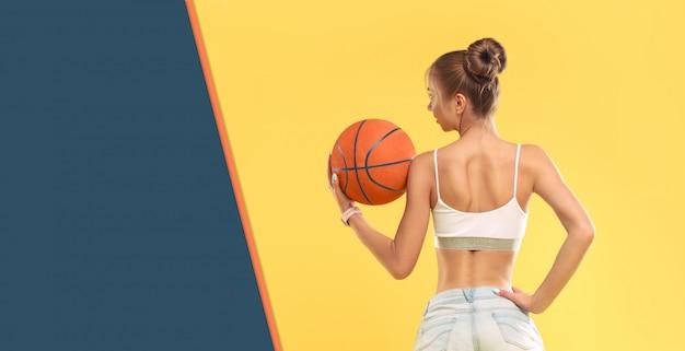 Sexy meisje dat korte borrels draagt die een basketbal op gele muur houden