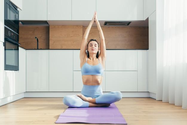 Sexy meisje doet yoga thuis in de keuken