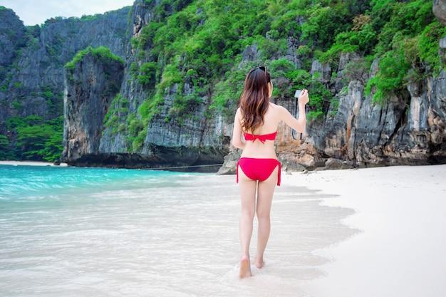 Sexy meisje draagt een rode bikini en neemt een foto op het strand.