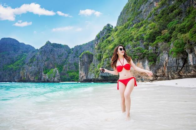 Sexy meisje draagt een rode bikini in een gelukkige bui op het strand.