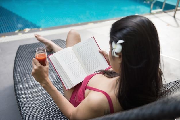Sexy meisje gelezen boek dichtbij zwembad