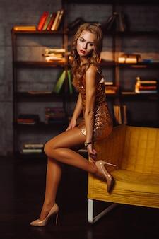 Sexy meisje in een gouden jurk met boeken in de bibliotheek. model met lang haar en rode lippenstift in het interieur.