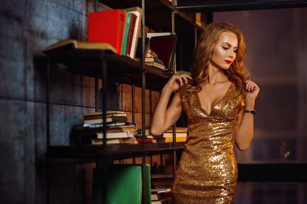 Sexy meisje in een gouden jurk op de achtergrond van boeken in de bibliotheek. model met lang haar en rode lippenstift in het interieur.