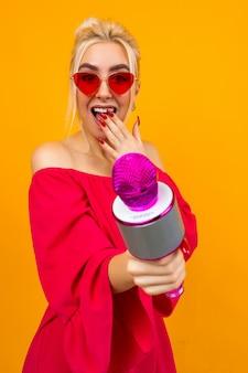 Sexy meisje in een rode jurk viert een verjaardag en zingt in karaoke