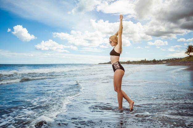 Sexy meisje in een zwembroek loopt het zwarte strand