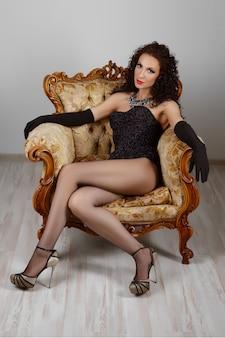 Sexy meisje in korset en lingerie zittend op vintage fauteuil