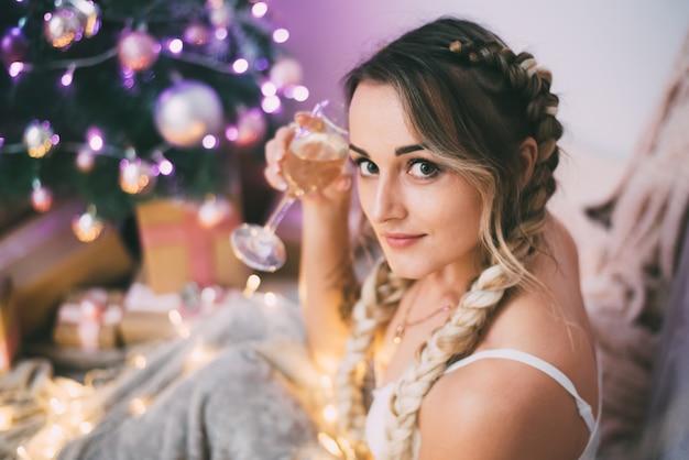 Sexy meisje in lingerie met twee staartjes en een glas champagne bij de kerstboom op het bed met een schattig plaid