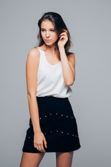 Sexy meisje in mode moderne jurk is poseren in studio geïsoleerd op een witte achtergrond