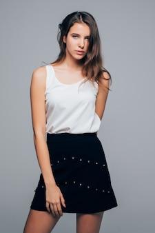 Sexy meisje in mode moderne jurk is poseren in studio houdt haar armen op haar geïsoleerd op een witte achtergrond