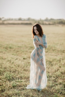 Sexy meisje in ondergoed topless poseren in een veld in de zomer buiten. het effect van een kleine filmkorrel toegevoegd