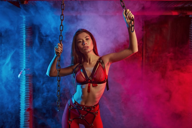 Sexy meisje in rood bdsm pak vasthouden aan kettingen, verlaten fabriek interieur. jong meisje in erotisch ondergoed, sexfetisj, seksuele fantasie