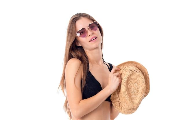 Sexy meisje in zonnebril en stro in handen geïsoleerd op witte achtergrond