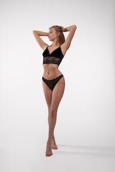 Sexy meisje in zwarte kanten ondergoed staat met haar handen omhoog, foto op een witte achtergrond