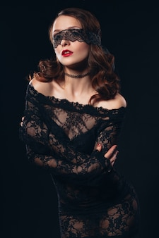 Sexy meisje in zwarte maskerlingerie op zwarte