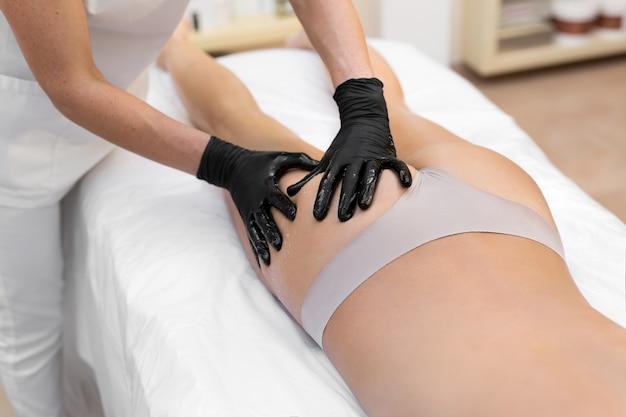 Sexy meisje liggend op de massagetafel in de spa salon. een vrouwelijke masseur doet een anti-cellulitis massage aan een meisje in een schoonheidssalon.