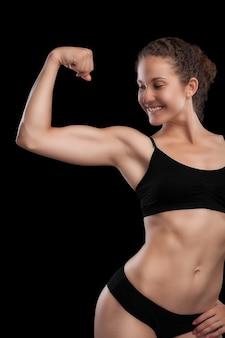 Sexy meisje met een atletisch lichaam, geïsoleerd op zwart