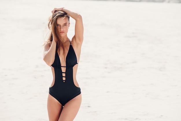 Sexy meisje met perfecte sportieve lichaam in zwarte zwembroek ontspannen op het strand.