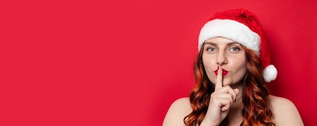 Sexy meisje met rode santahoed met pompom die stil met vinger op lippen op een rode muur vragen te zijn