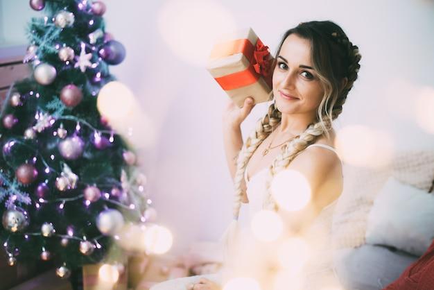 Sexy meisje met twee staartjes in lingerie bedekt met een plaid met slingers op het bed met een doos met een schattig cadeau