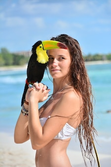 Sexy meisje poseert met toekan in mexico op een strand op een zonnige dag