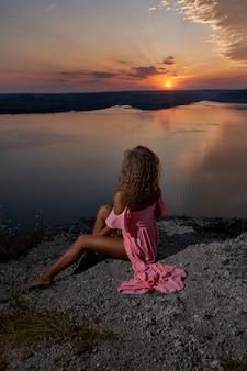 Sexy meisje zit en bewondert de zonsondergang in de buurt van het meer