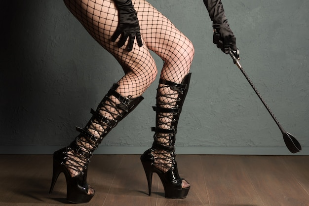 Sexy meisjesbenen in visnet en hoge hakken fetisjlaarzen met zweep bereiden zich voor op straf.