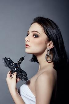 Sexy mode brunette meisje heeft zwarte haarjuwelen rond haar nek en oren, grote blauwe ogen. zomer huidverzorging, grote blauwe ogen, natuurlijke huidverzorging