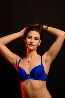 Sexy mode brunette vrouw met lang donker haar in blauwe lingerie op zwart