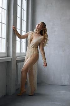 Sexy mode mooie vrouw in jurk staande tegen de muur