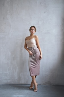 Sexy mode mooie vrouw in jurk staat tegen de muur. perfecte make-up, romantisch portret van een blonde vrouw